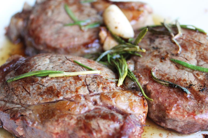 Pan Seared Filet Mignon with Rosemary & Garlic: An easy recipe that is out of this world tender, juicy, & so flavorful! The rosemary & garlic are a perfect match for this high quality cut of meat (also known as a tenderloin) | thenourishedfamily.com