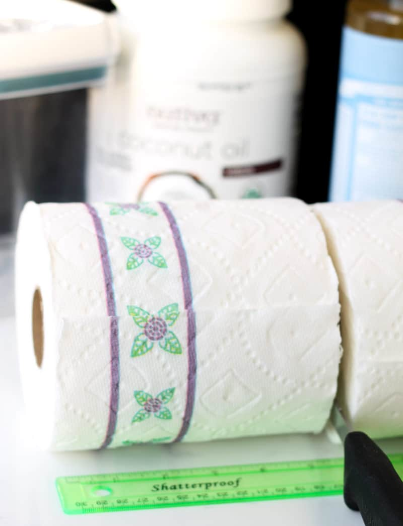 Cutting paper towel roll in half to make home made baby wipes.