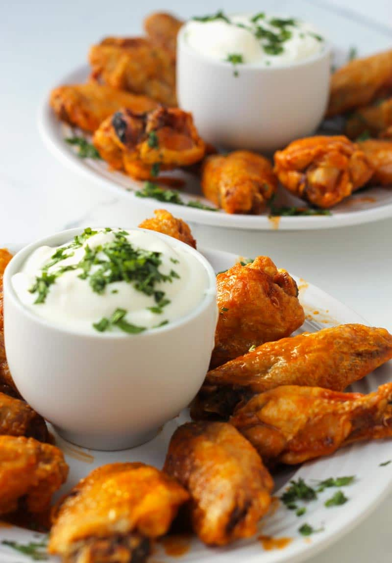 Two plates of hot wings ready to eat.