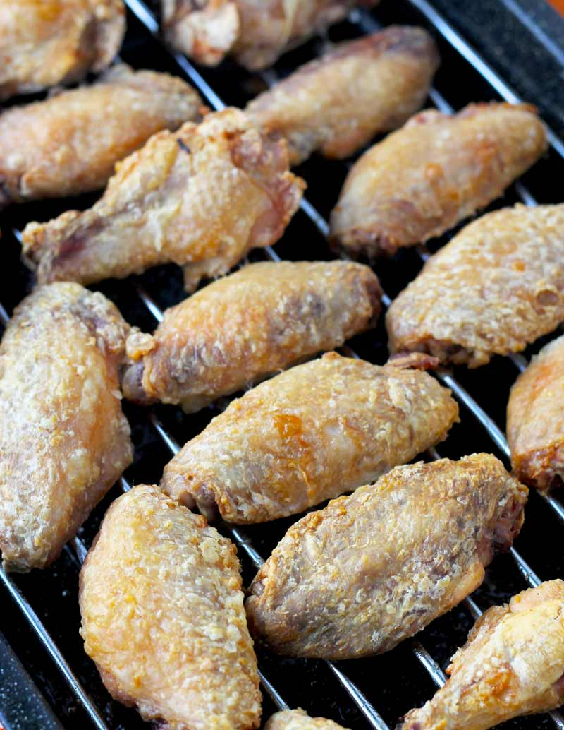 Crispy baked chicken wings cooling on a wire rack.
