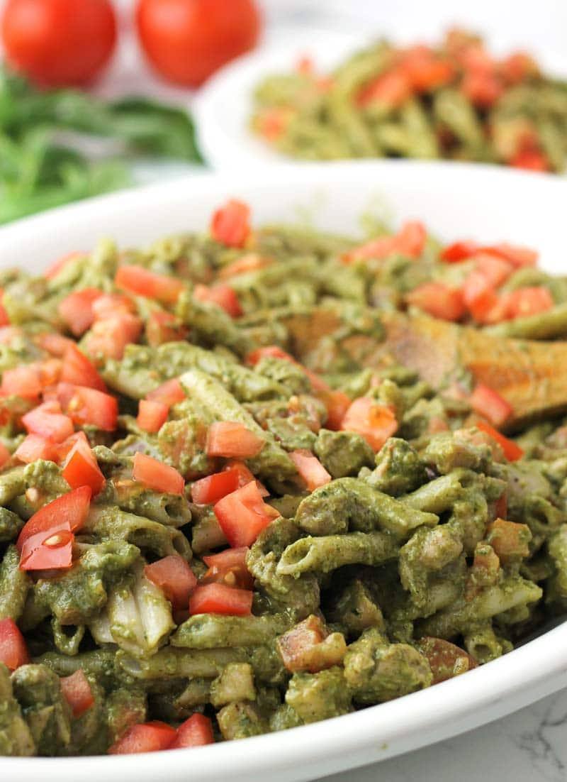 This healthy Pesto Chicken Pasta is a wonderful main course or a hearty potluck side dish. Fresh basil pesto (with walnuts), penne pasta, organic chicken, & finished with ripetomatoes.| thenourishedfamily.com