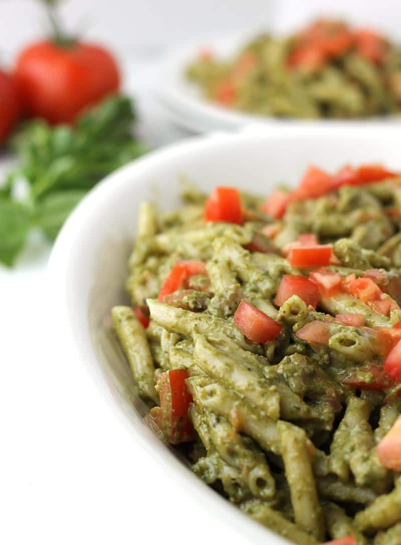 This healthy Pesto Chicken Pasta is a wonderful main course or a hearty potluck side dish. Fresh basil pesto (with walnuts), penne pasta, organic chicken, & finished with ripe tomatoes. | thenourishedfamily.com